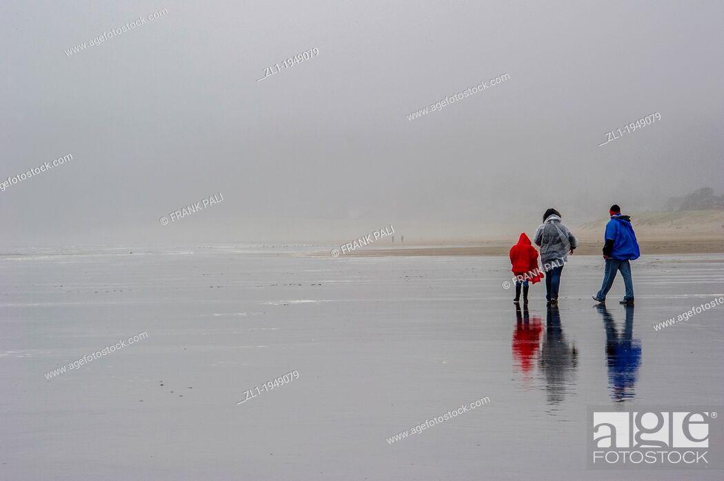 Stock Photo: Family walking on rainy day on Cannon Beach.Cannon Beach, Oregon USA.