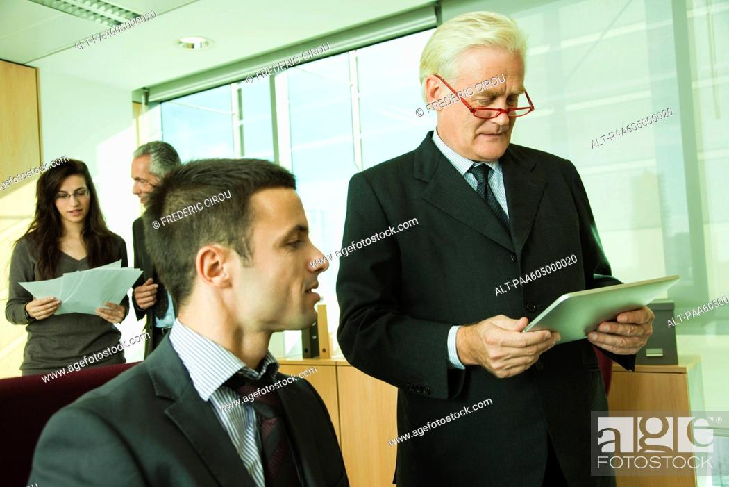 Stock Photo: Executive using digital tablet with young associate.