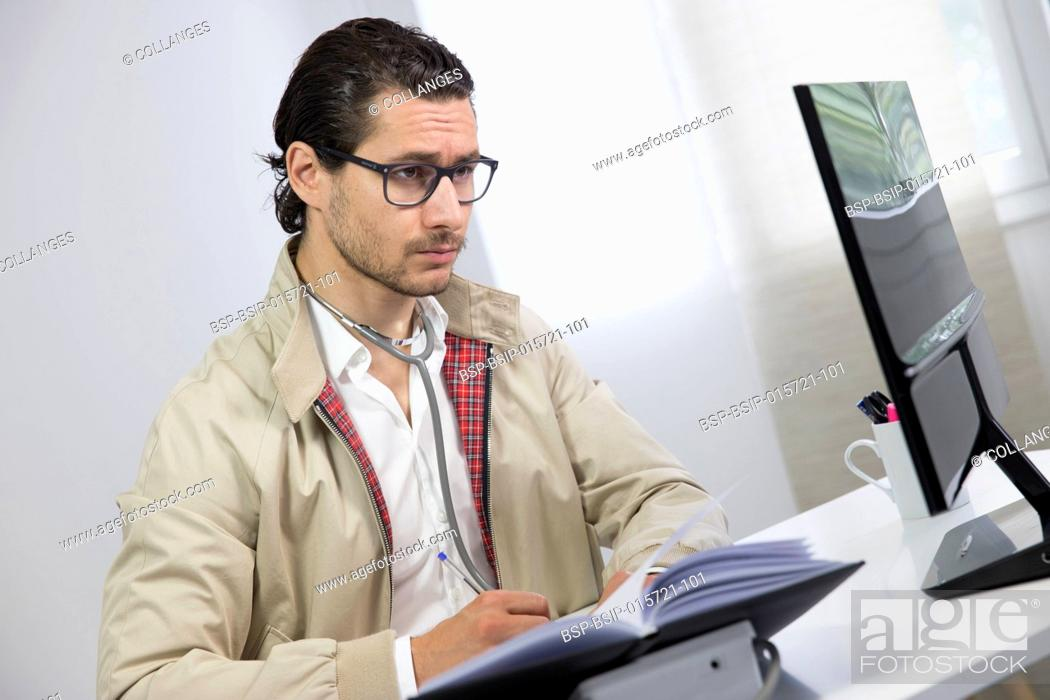 Stock Photo: Doctor in front of laptop.