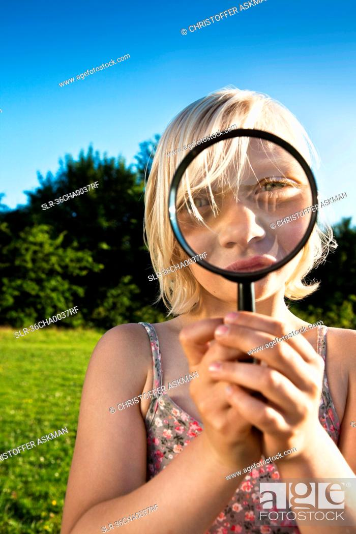 Stock Photo: Girl playing with magnifying glass.