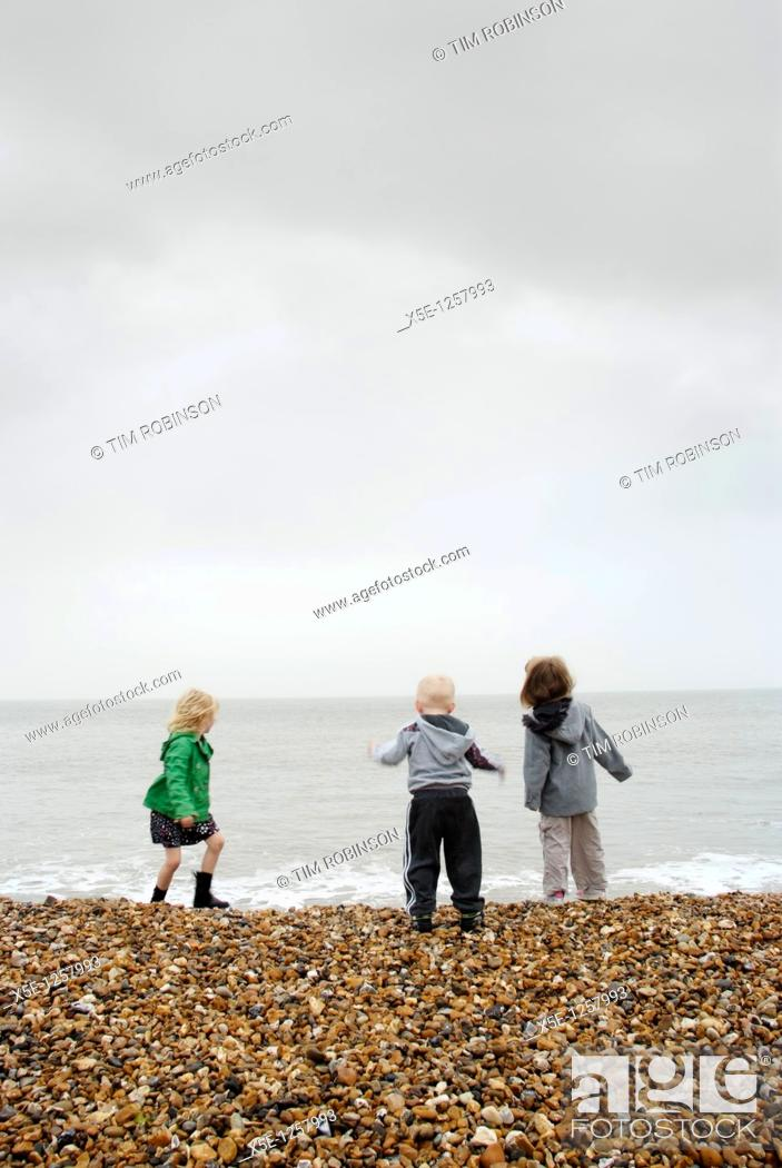Stock Photo: Rearview 3 young children playing with waves on shingle beach.