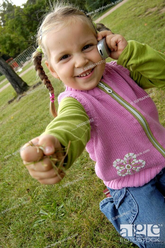 Stock Photo: Cell Phone, Brown Hair, Color Image, People, Smile, Nature, View, Park, Body, Child, Kid, Girl, Baby, Autumn, Hand, Grass, Alone, Object, Spring, Old, Place, Public, Communication, Telephone, Position, Pink, Year, Calling, Season, Garden