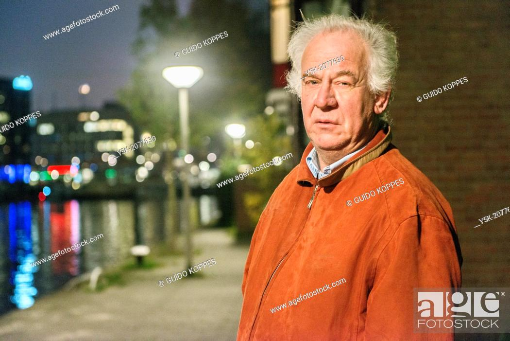 Stock Photo: Rotterdam, Netherlands. Elder caucasian male, walking along the old harbor during nightfall.