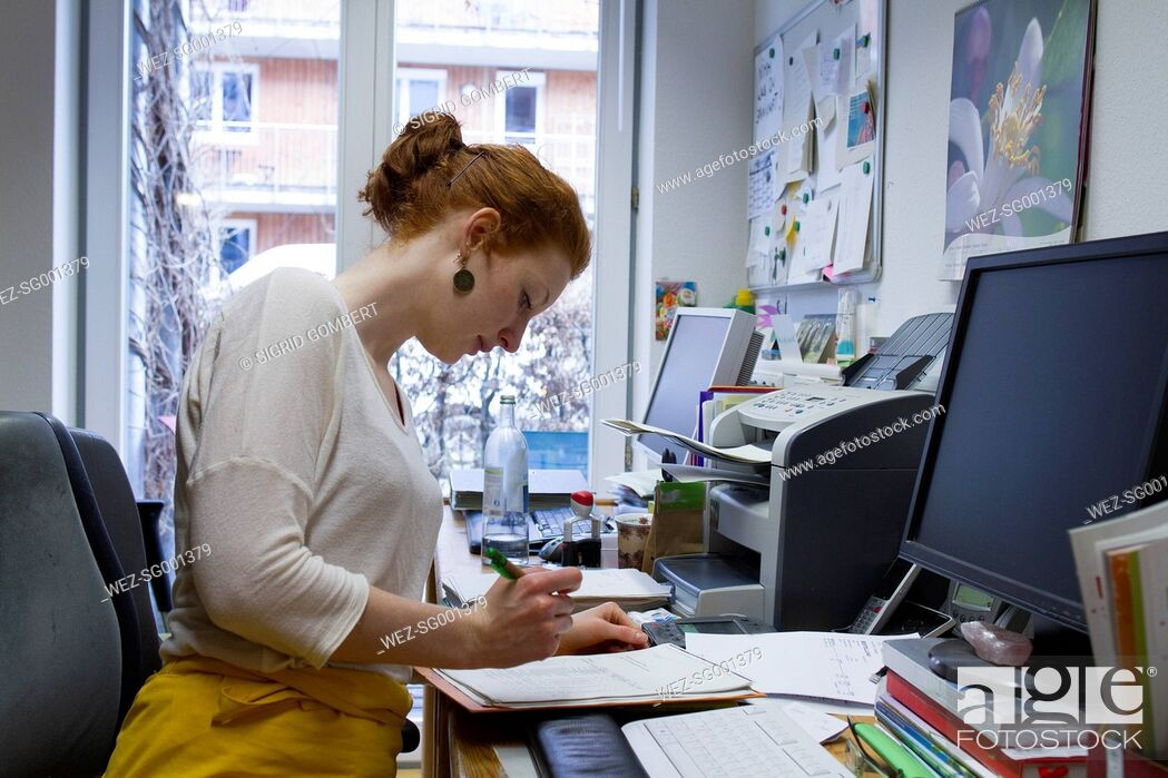Stock Photo: Young woman checking form in an office.