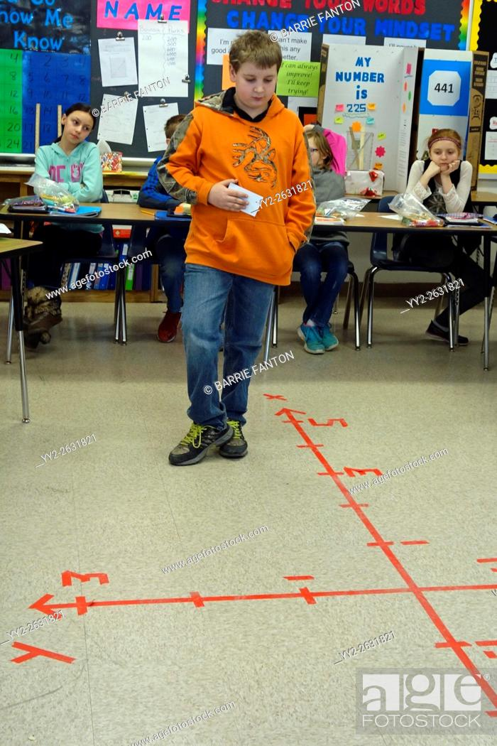 Stock Photo: 6th Grade Boy Solving Math Coordinates Problem, Wellsville, New York, USA.