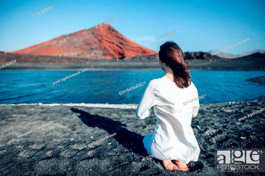 Stock Photo: Back view of woman in white clothes praying in unique black sand beach Playa Bermeja, Lanzarote, Canary Islands, Spain. Lake and mountain on background.