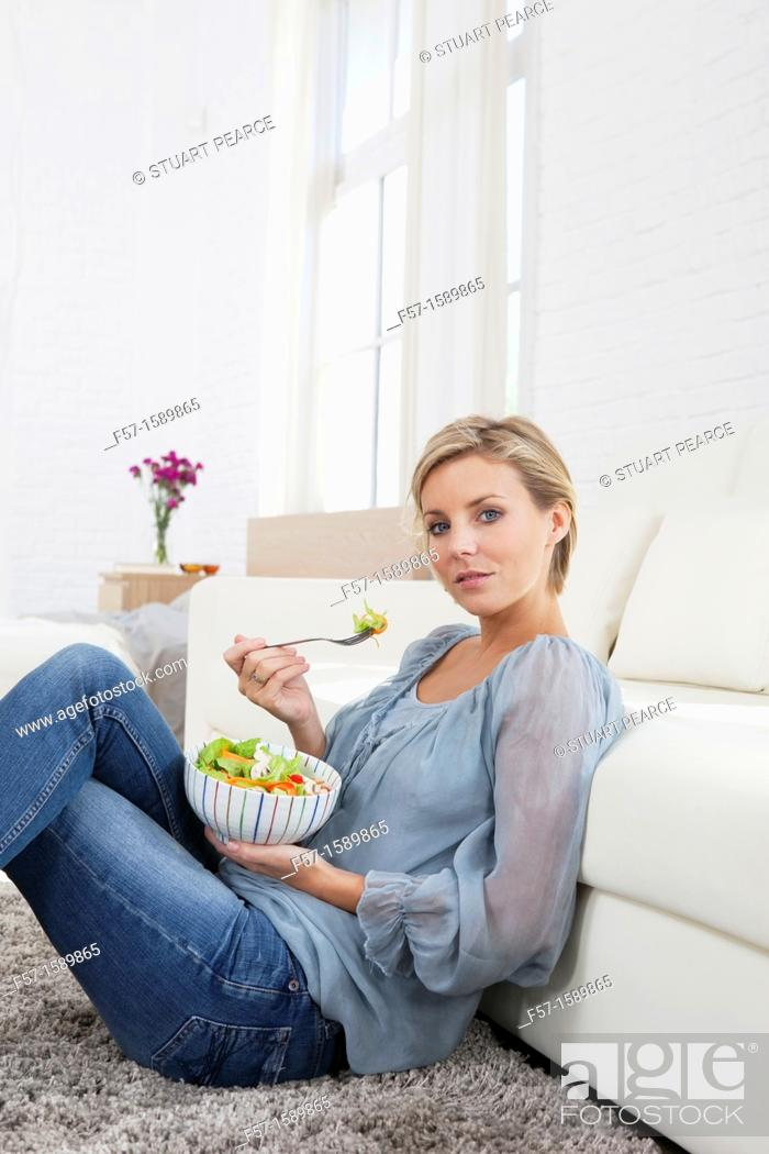 Stock Photo: Young woman having a salad for lunch.