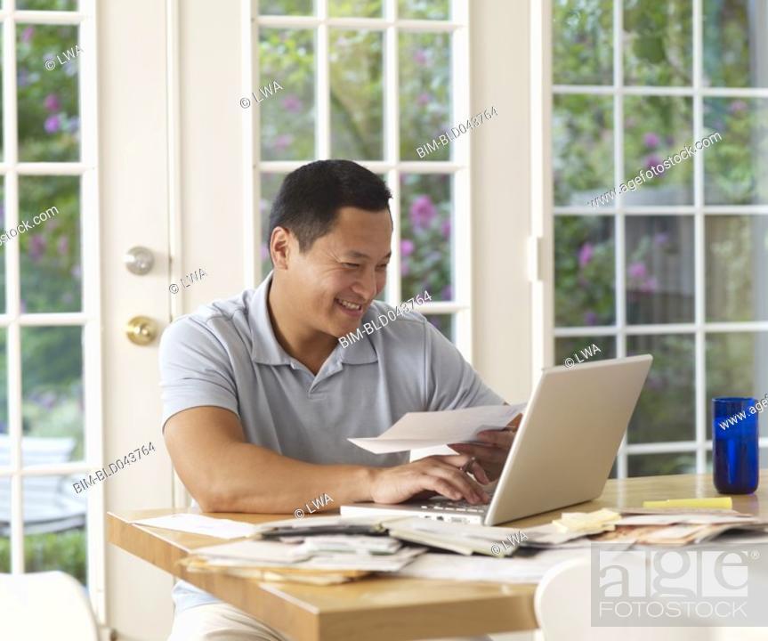 Stock Photo: Asian man paying bills online.