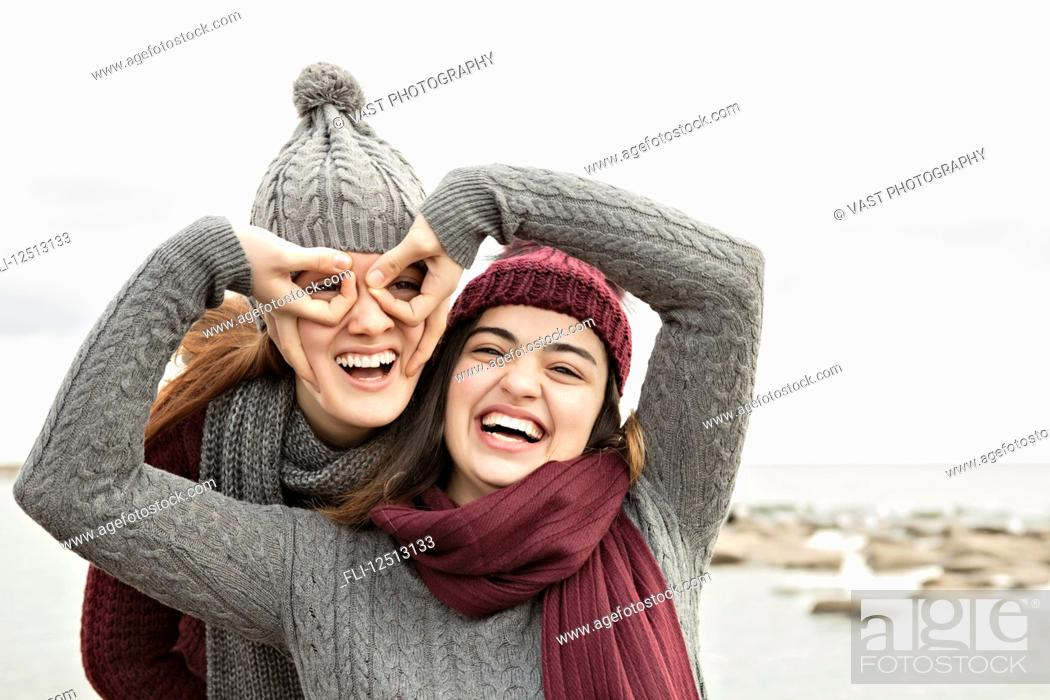 a17fcd93ecb Two friends playing on the beach wearing knit hats and scarves ...