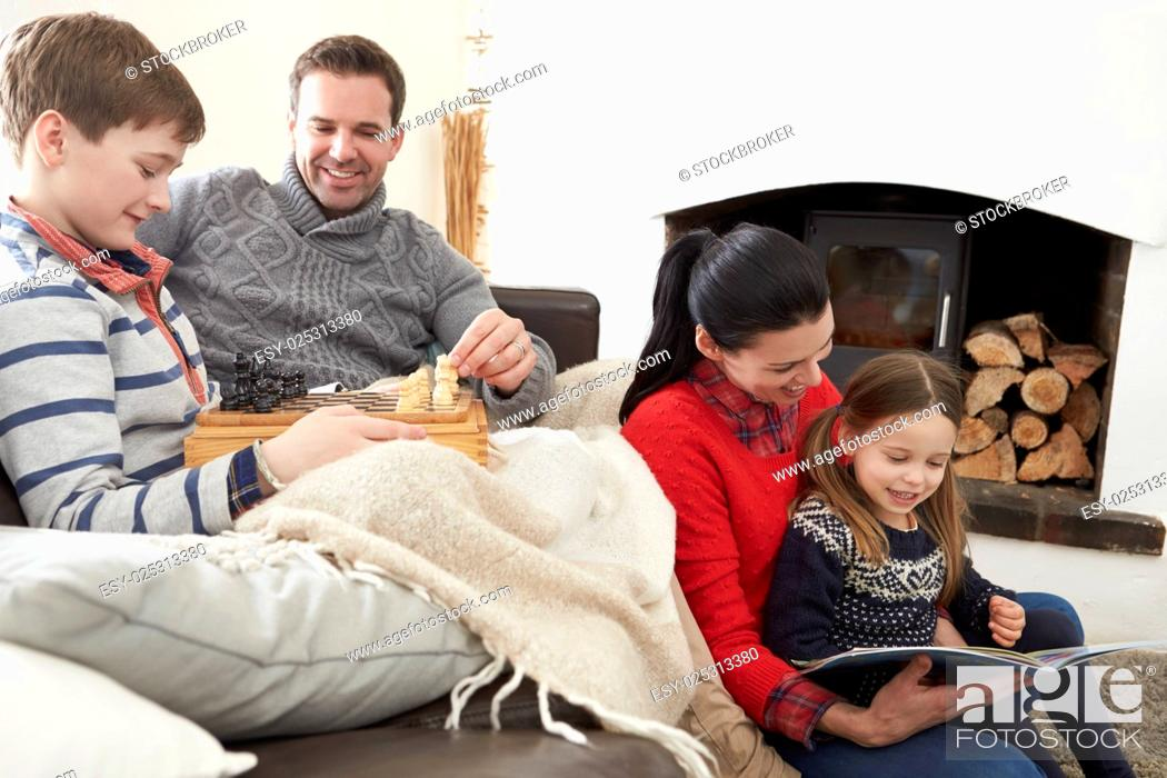 Stock Photo: Family Relaxing Indoors Playing Chess And Reading Book.