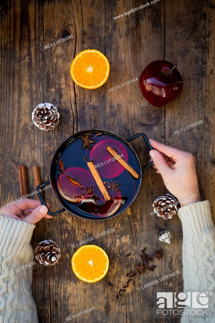 Stock Photo: Woman's hands holding cooking pot of mulled wine with orange slices and spices.