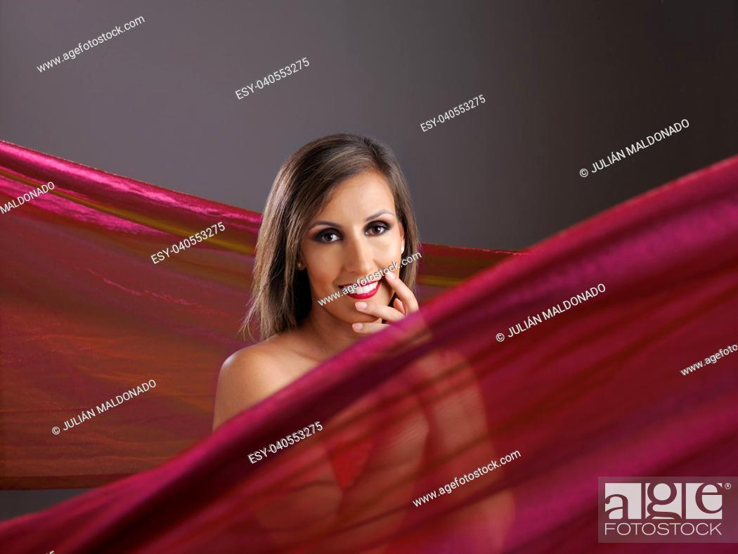 Stock Photo: Young woman showing her beauty surrounded by fabrics.