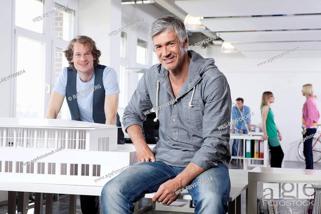 Stock Photo: Germany, Bavaria, Munich, Men with architectural model in office, colleagues talking in background.
