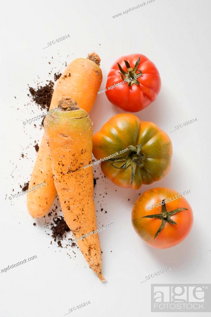 Stock Photo: Two carrots with soil and three tomatoes.