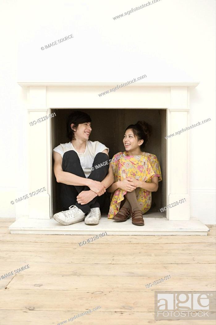 Stock Photo: Young couple sitting in a fireplace.