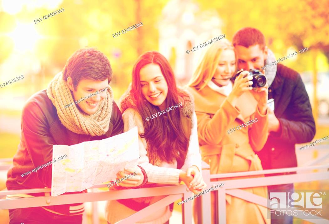 Stock Photo: holidays and tourism concept - group of friends or couples with tourist map and camera in autumn park.