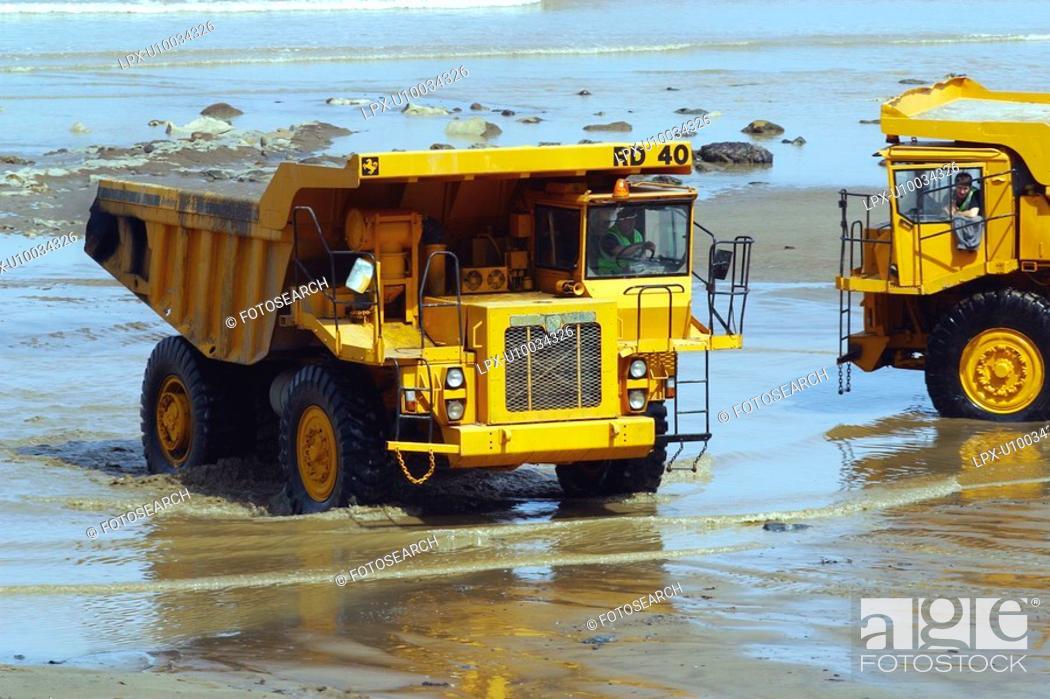 Stock Photo: Rigid dumper trucks during construction of stone groyne rock armour sea defences.