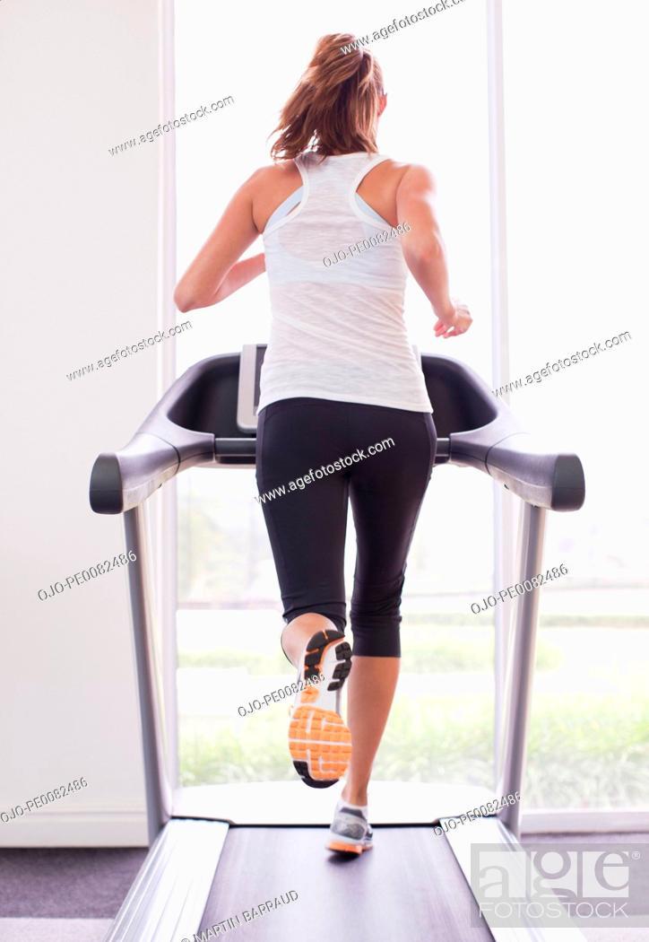 Stock Photo: Woman running on treadmill.