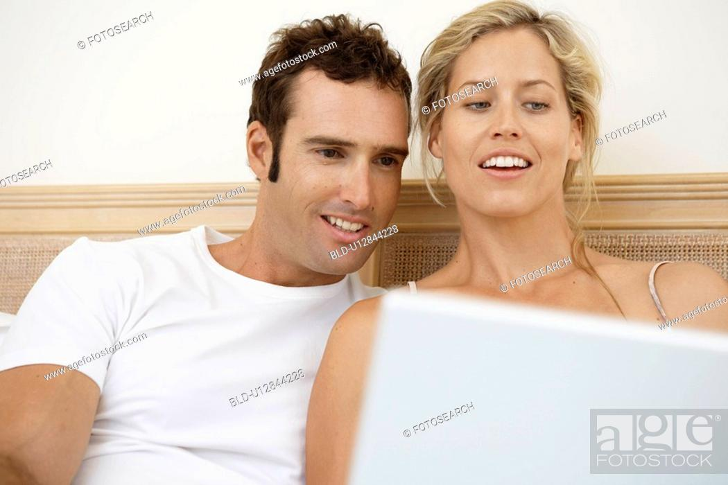 Stock Photo: Mid adult couple using laptop in bed.