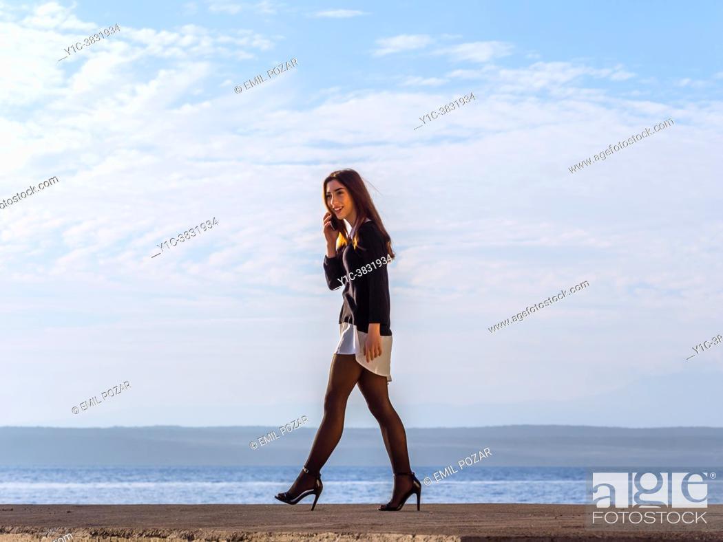 Stock Photo: Teenage girl fanciful walking on seaside.