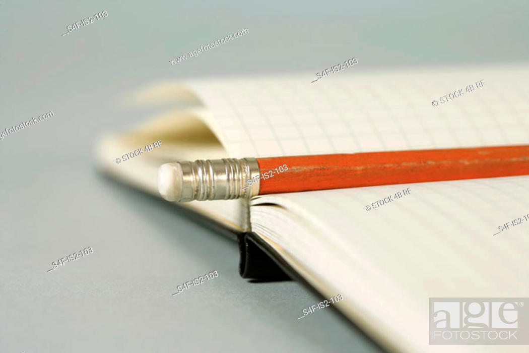 Stock Photo: Pencil lying on an empty notebook, close-up, selective focus.