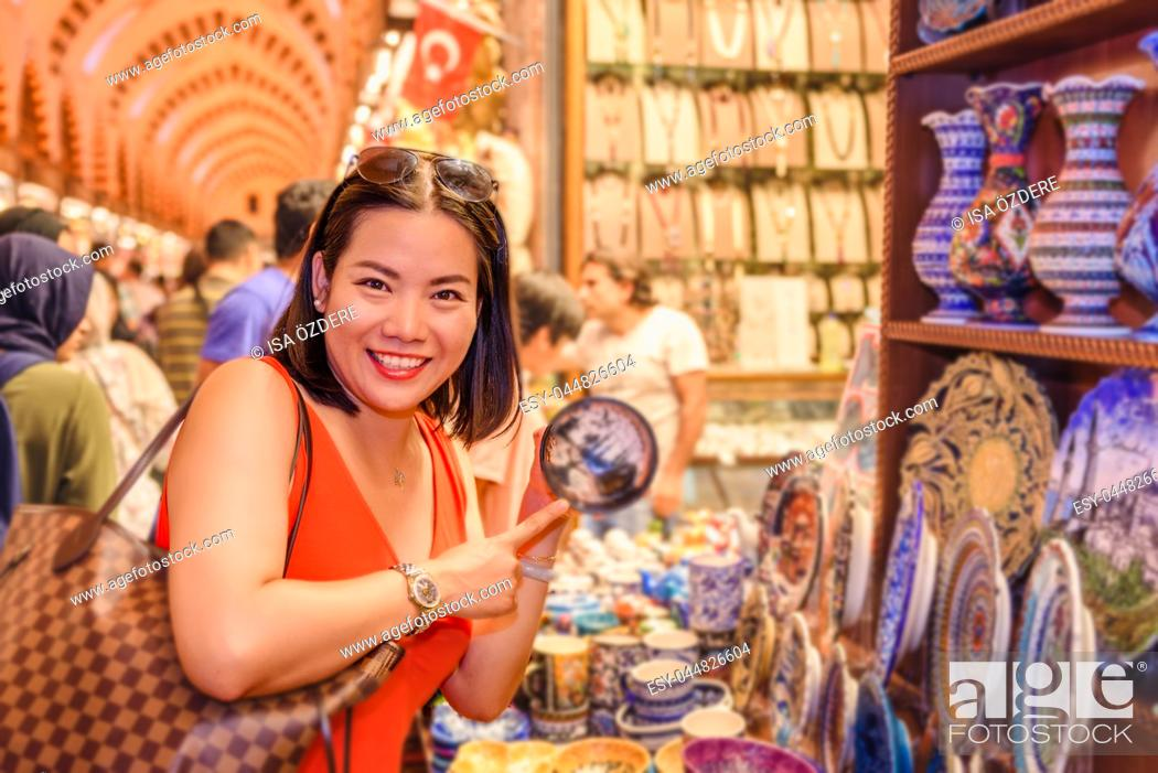 Stock Photo: Beautiful Chinese woman buys souvenirs sold in Egypt Bazaar in Eminonu,Istanbul,Turkey.