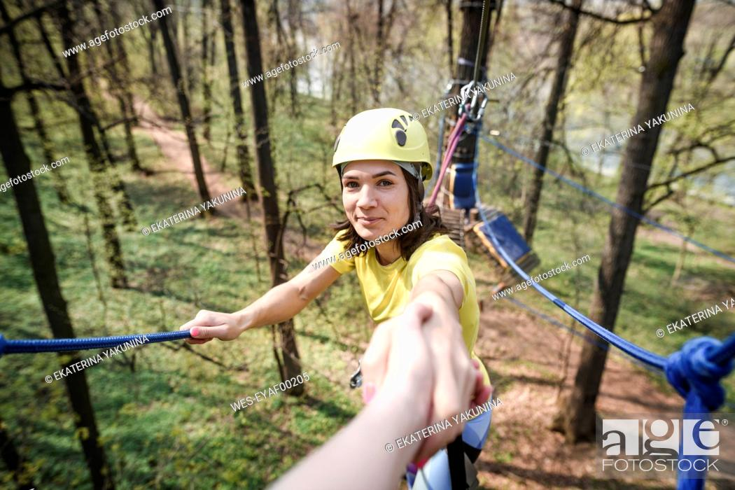 Photo de stock: young smiling woman giving her hand in a rope course.
