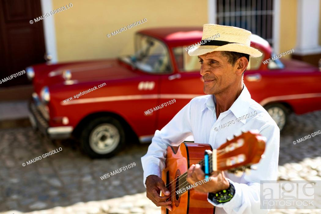 Imagen: Cuba, Trinidad, man playing guitar on the street.