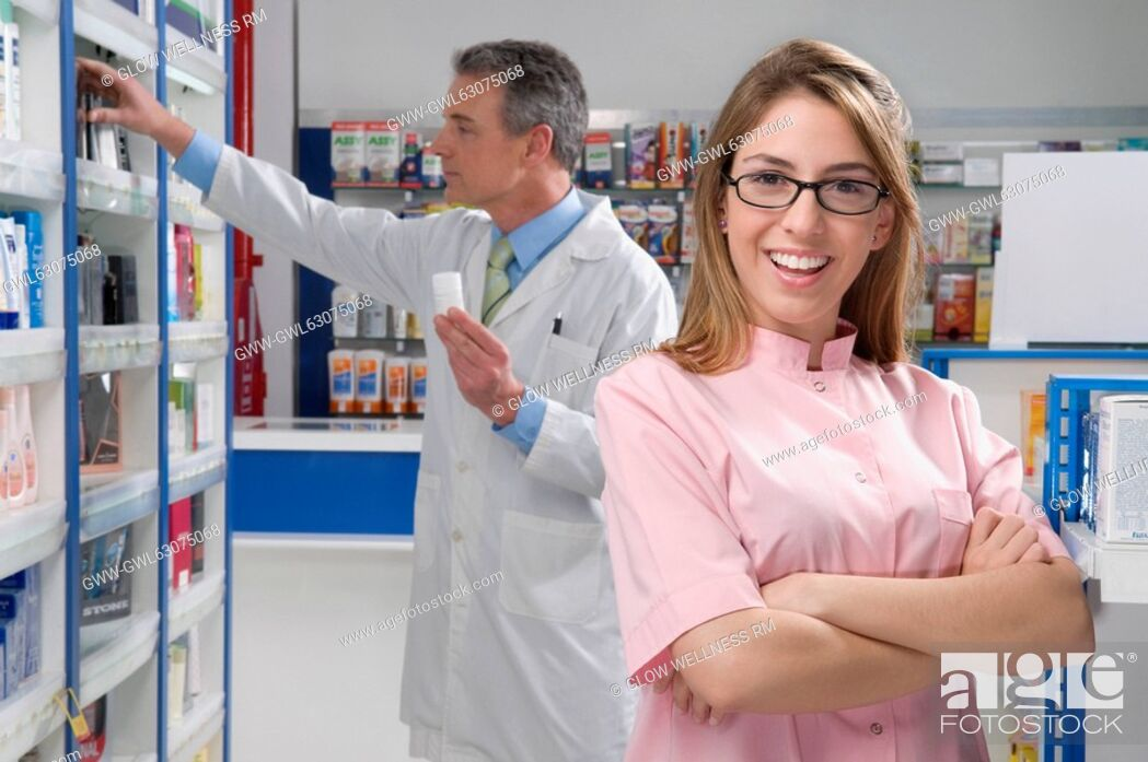 Imagen: Female pharmacist smiling with a male pharmacist in the background.