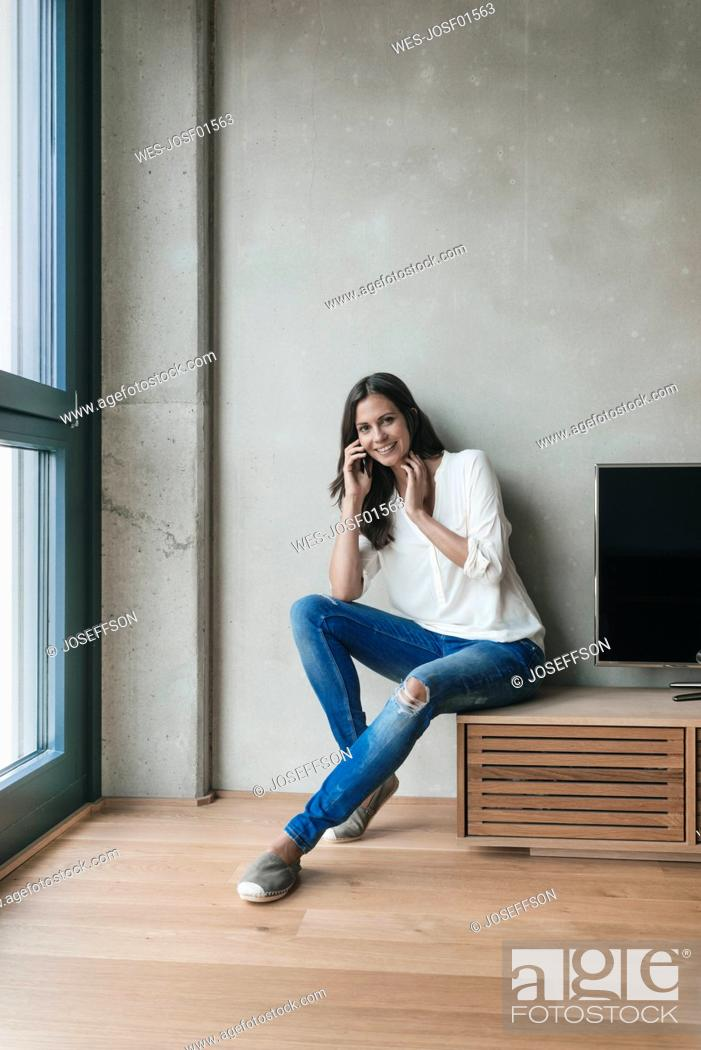 Stock Photo: Portrait of smiling woman on cell phone at home.