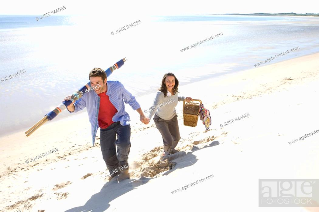 Stock Photo: Couple carrying picnic basket and blankets on beach.