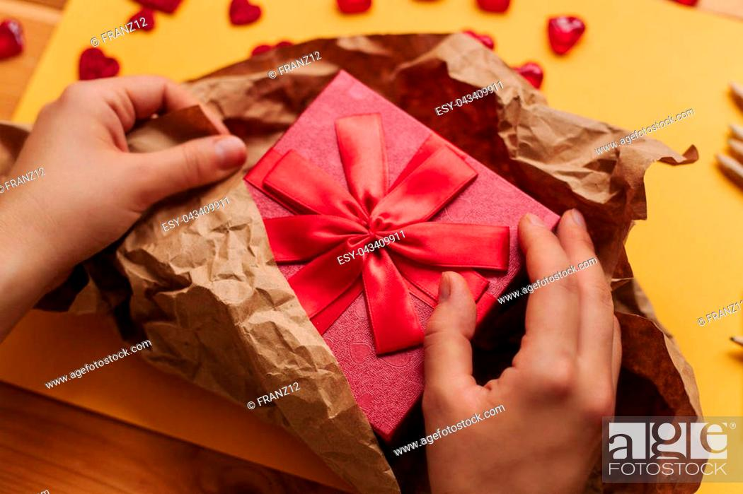 Imagen: A creative person packs a handmade gift in a beautiful red box tied with a ribbon. Creation. Celebrating the event.