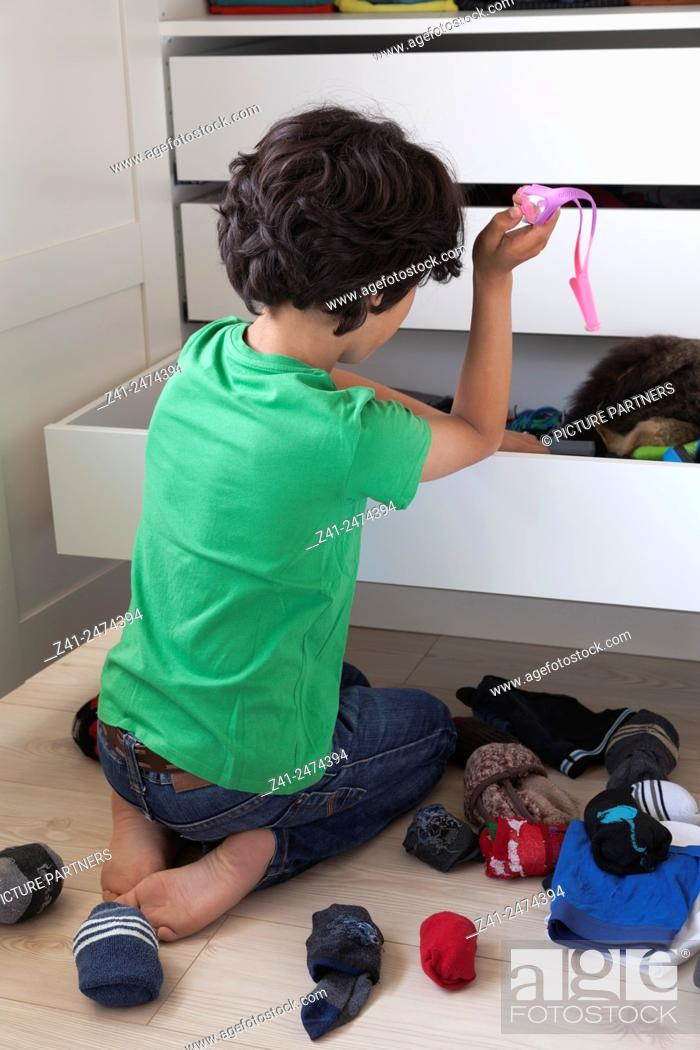 Photo de stock: Teenage boy making a mess while searching into his wardrobe drawer.