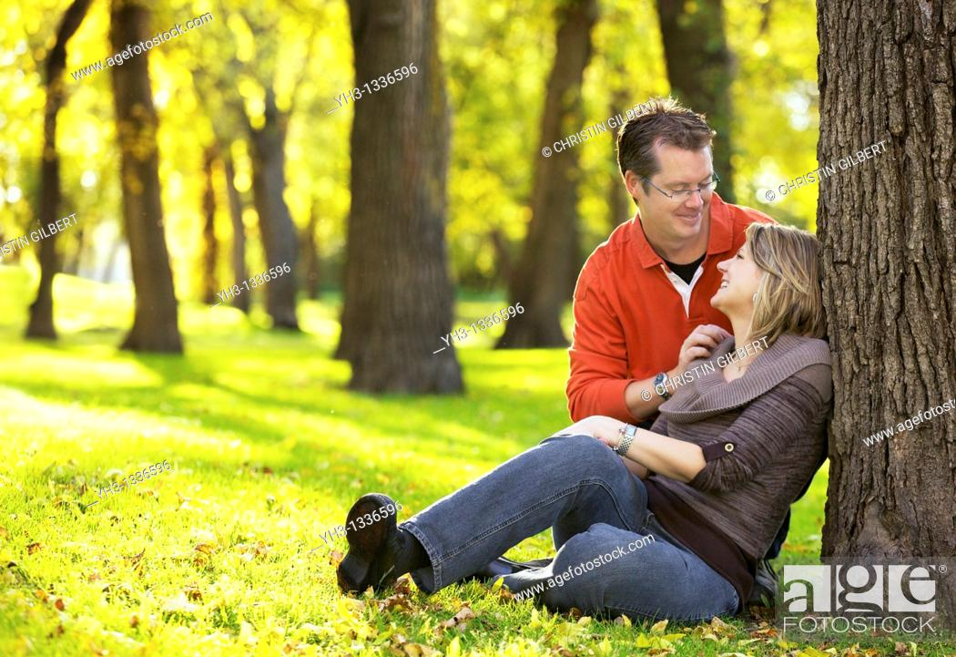 Stock Photo: Happy young couple sitting at the park, looking at each other lovingly.