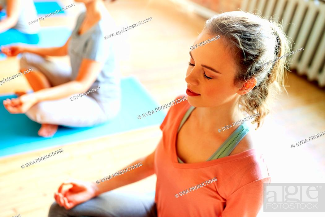 Stock Photo: woman meditating at yoga studio.