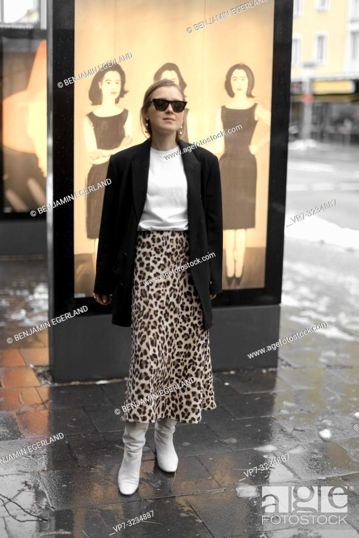 Stock Photo: fashionable woman standing in front of Alex Katz art pictures at street, in Munich, Germany.