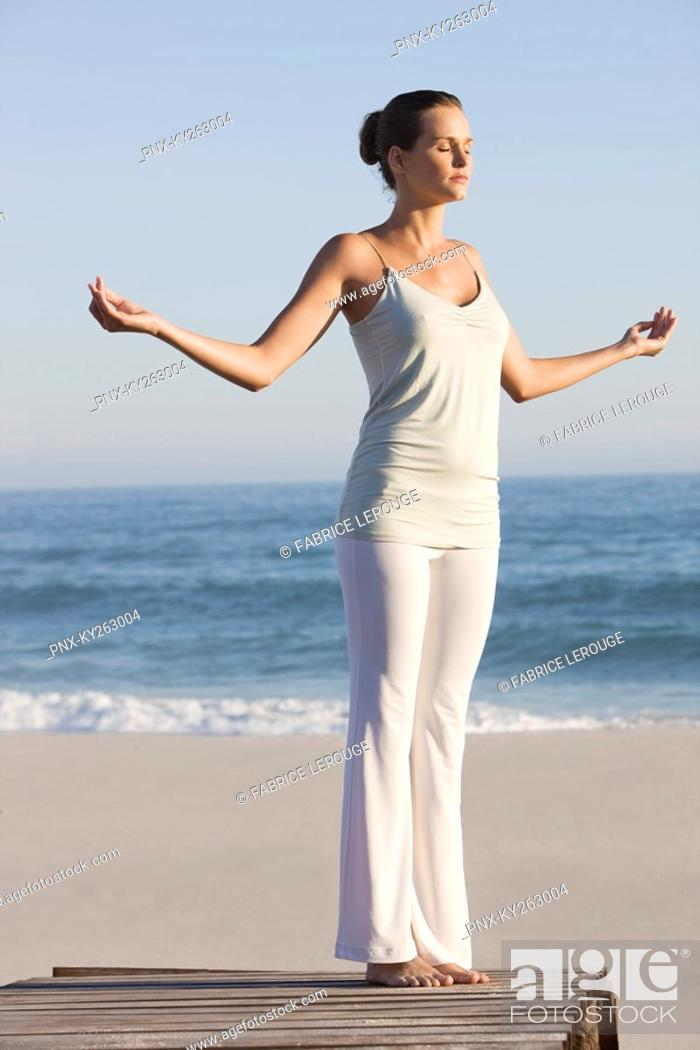 Stock Photo: Woman practicing yoga on a boardwalk.