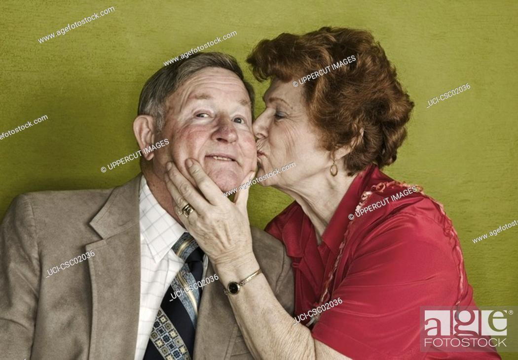 Imagen: Senior woman kissing husband's cheek.
