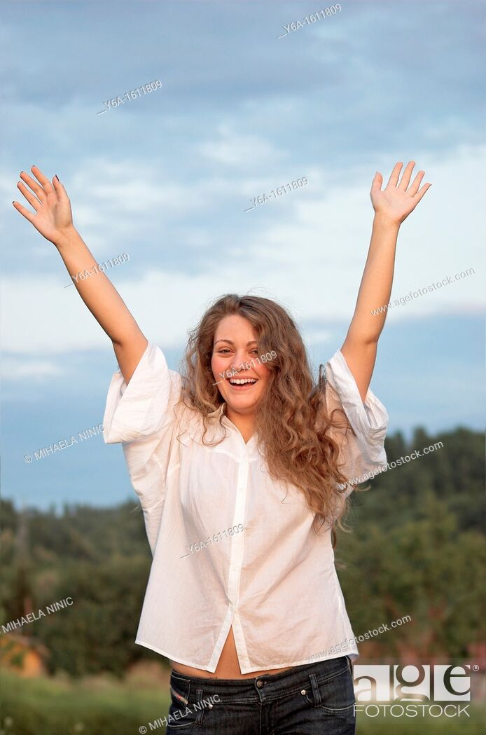 Stock Photo: Portrait of a smiling young woman outdoors with arms raised.
