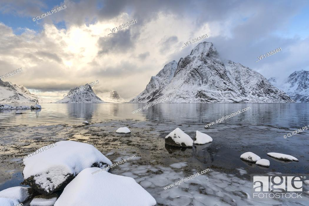 Stock Photo: Olstinden peak in winter, with ice and snow on the rocky beach in the foreground. Reine, Nordland county, Northern Norway region, Norway.