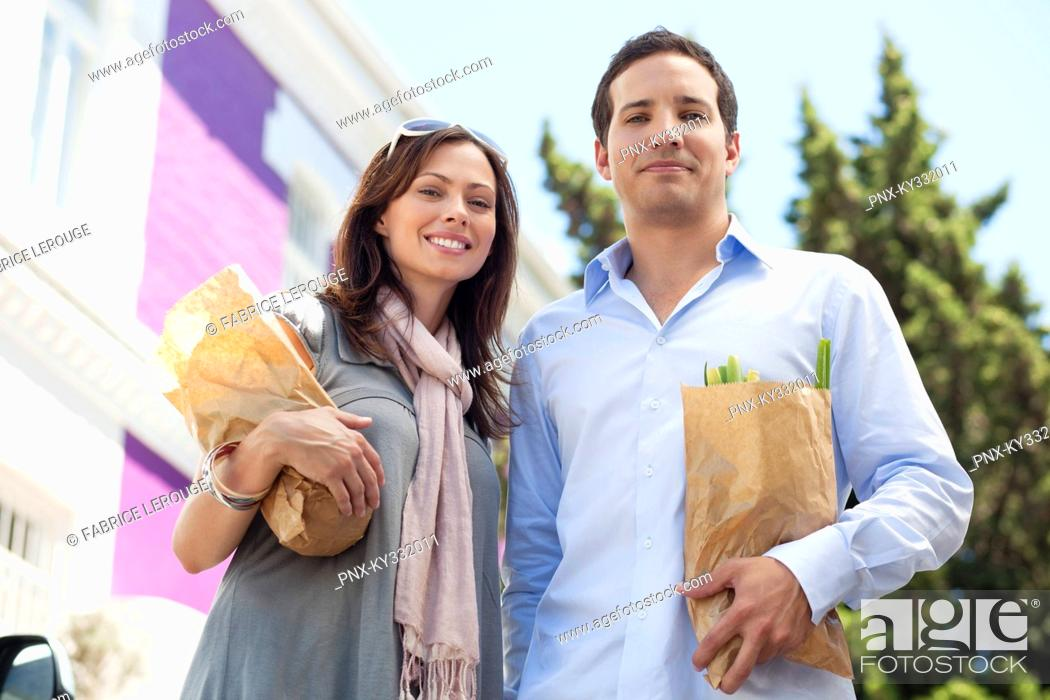 Stock Photo: Portrait of a couple standing with paper bags full of vegetables.