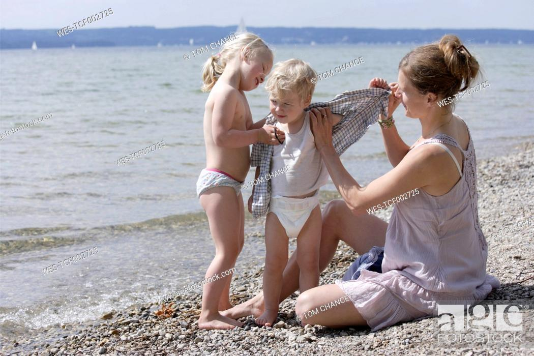 Stock Photo: Germany, Bavaria, Mother and daughter helping son to undress.