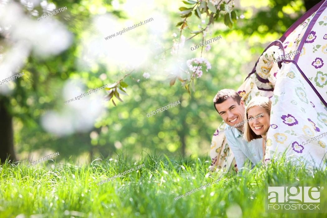 Stock Photo: Couple peering out of tent at campsite.