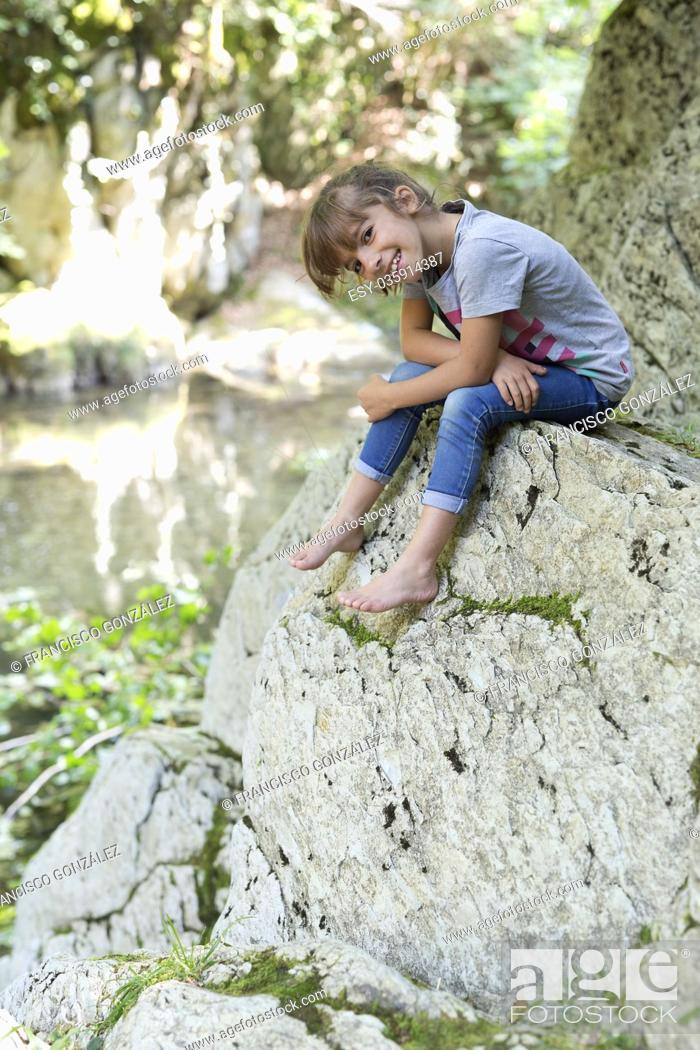 Photo de stock: Girl sitting on a rock next to the Waterfall of the bucket in the Selva de Irati in Navarra, Spain.
