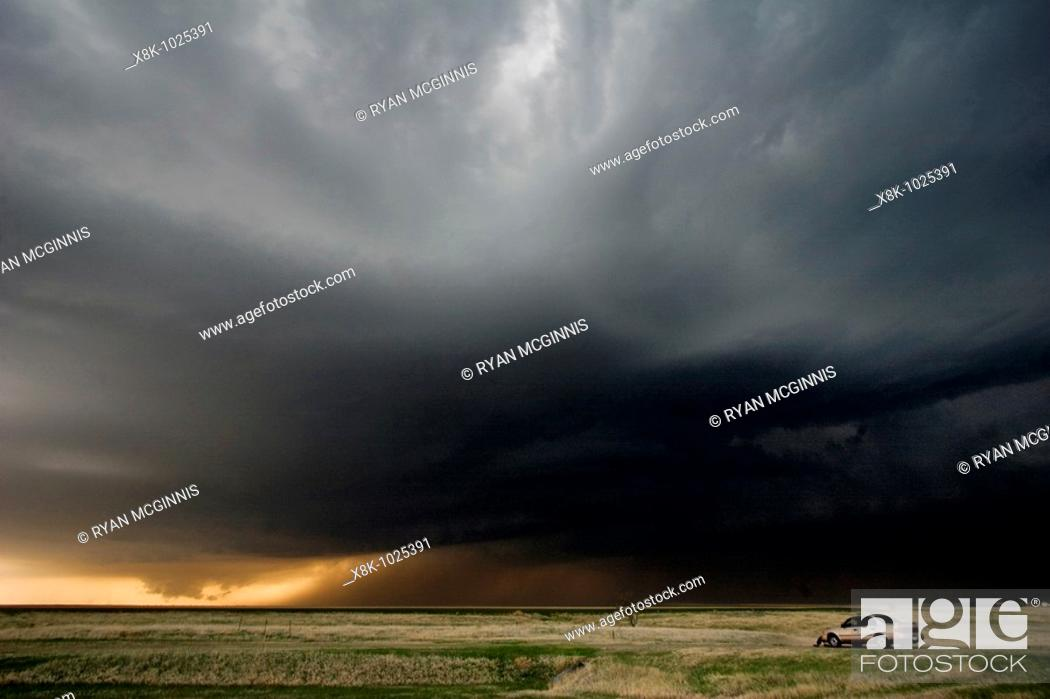 Stock Photo: A storm chaser's car is parked as a storm chaser watched a lowering wall cloud a precursor to a tornado near Hill City, Kansas, USA, 4/24/2008.
