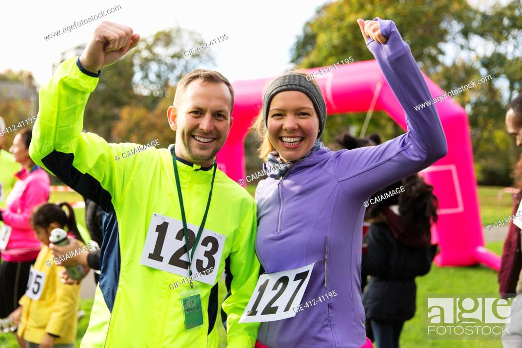 Stock Photo: Enthusiastic runner couple cheering at charity run in park.