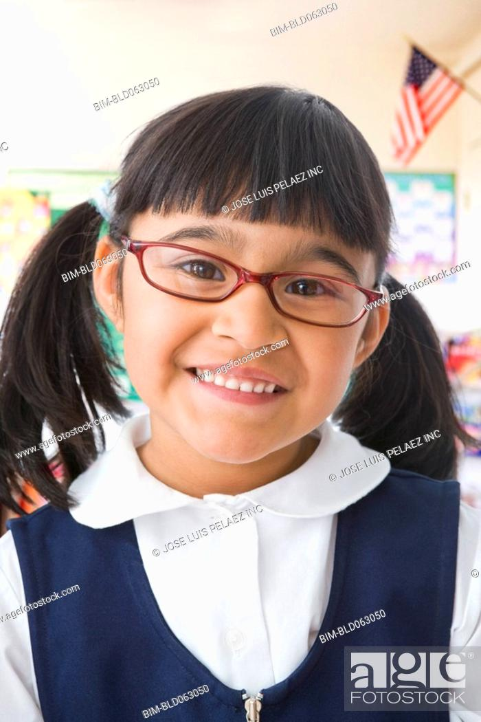 Stock Photo: Close up of Hispanic girl wearing eyeglasses in classroom.