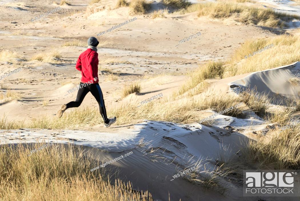 Imagen: Man jogging on frost coverd dunes on Seaton Carew beach, north east England, United Kingdom.