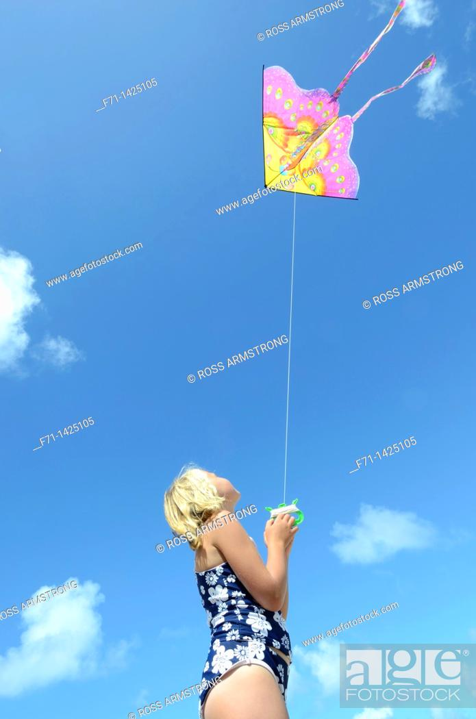Stock Photo: Six year old girl flying a kite at the beach  Mimiwhangata, Northland, New Zealand.
