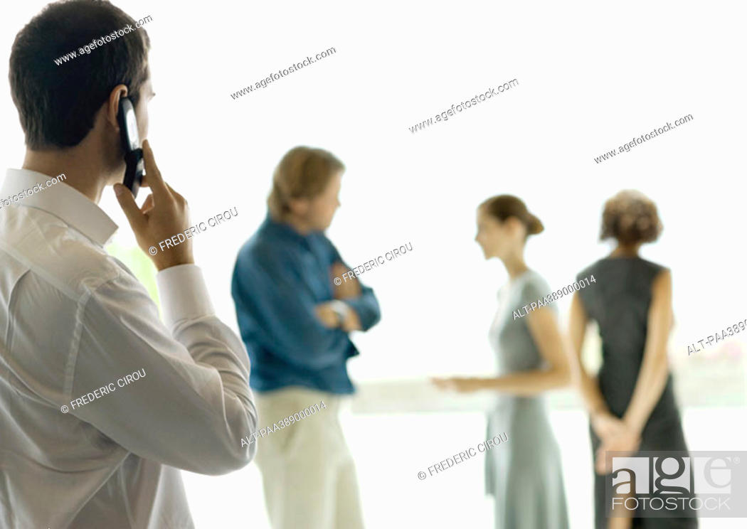 Stock Photo: Man using cell phone, people standing and chatting in background.